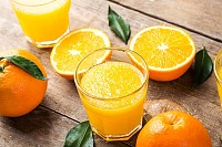 Squeezed orange juice in a glass and fresh oranges