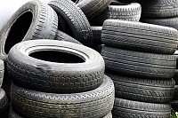 Old used car tires stacked in high piles