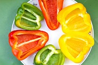 Cut in halves clourful peppers slices on a plate