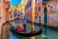 Narrow canal with gondola and bridge in Venice, It