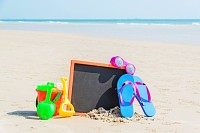 Flip flop, sunglasses, children toys on the beach