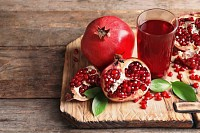 Glass of pomegranate juice and fresh fruits