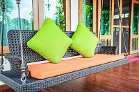 Plastic wicker porch swinging bench with green pil