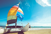 Colorful sailboat on tropical beach in summer.