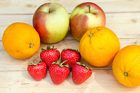 Apples, oranges and strawberries on wooden table