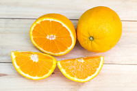Composition of fresh ripe cut oranges on wooden ba