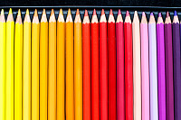 Line of colorful pencils on black velvet backgroun