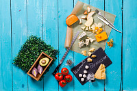 Different types of cheese on a blue wooden table