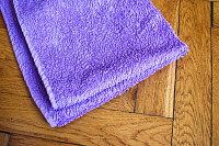 Colorful bent towel on wooden background: purple c
