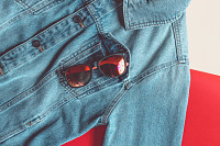 Sunglasses in a jeans jacket pocket on a colored b