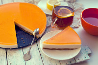 Orange jelly cake on white wooden background. Piec