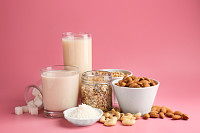 Assortment of tasty vegan milk on color background