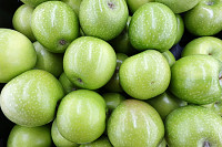 Many ripe juicy green apples in supermarket.