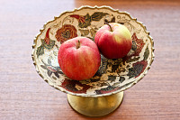 Apples in decorated metallic bowl with flowers orn