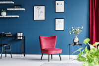 Red armchair in blue living room interior with wor