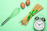 Culinary concept, cooking time. Alarm clock, pasta
