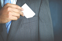 Young businessman holding white business card and
