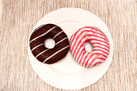 Pink and brown stripped donuts on plate on grey fa